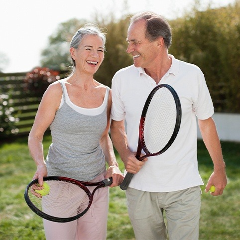 Older man and woman playing tennis after treatment for foot and ankle injuries