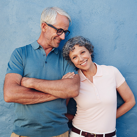 Older man and woman smiling after treatment for arthritis in the hands