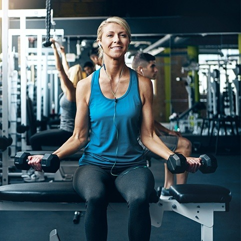 Woman working out at gym after treatment for elbow injury