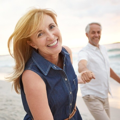 Man and woman smiling at beach after hand and wrist injury treatment