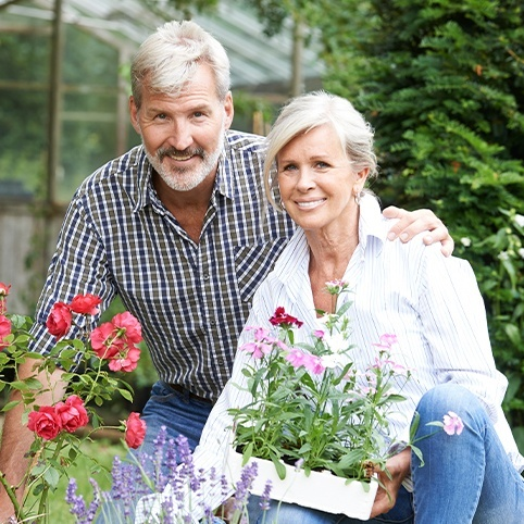 Older man and woman working in the garden after treatment for hip osteoarthritis