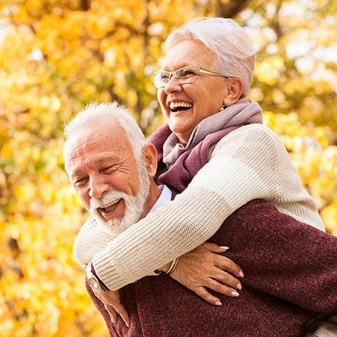 Older man and woman smiling together after treatment for join instability and impingement