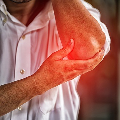 Man experiencing elbow joint instability holding elbow