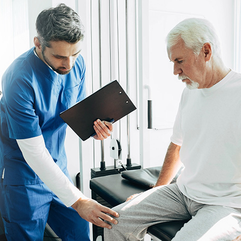 Doctor examining older man with knee arthritis