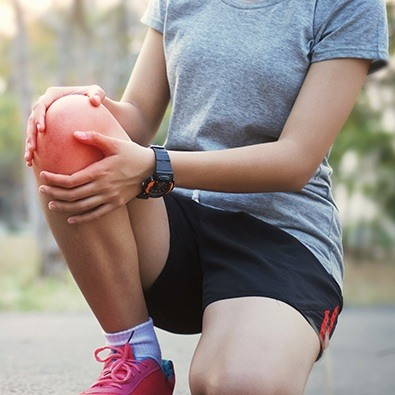 Woman on a run with patellofemoral syndrome holding knee in pain