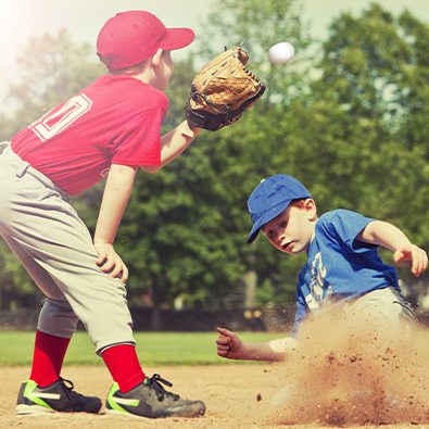 Two young boys playing baseball after little league elbow treatment