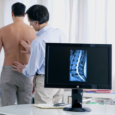 Doctor examining patient's back