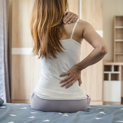 Woman in pain holding her lower back