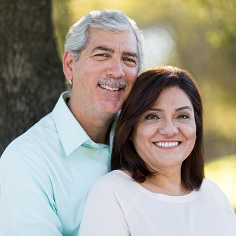 Older man and woman smiling after orthobiologic injection