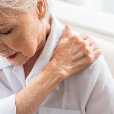 Older woman with shoulder arthritis holding arm