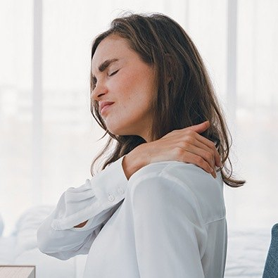 Grimacing woman with joint instability and impingement holding neck
