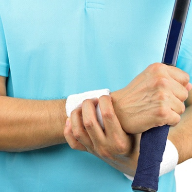 man with tennis racket holding sore wrist