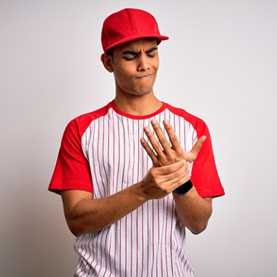 young baseball player with symptoms of hand arthritis