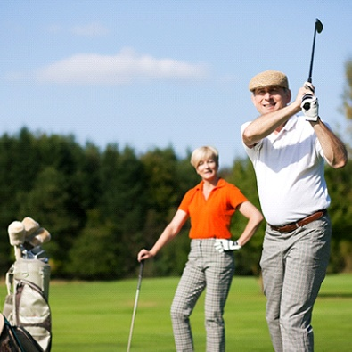 middle-aged man playing golf with wife