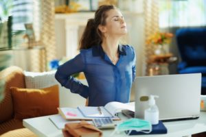 woman stretch back while sitting at desk