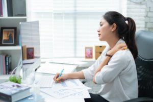 woman experiencing neck pain while working